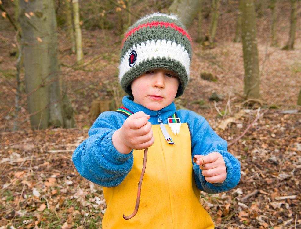 Child inspecting an earthworm, The Secret Garden, Fife, Scotland