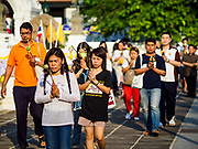"01 MARCH 2018 - BANGKOK, THAILAND:    People participate in a procession around at Wat Pathum Wanaram in central Bangkok. Many people go to temples to perform merit-making activities on Makha Bucha Day, which marks four important events in Buddhism: 1,250 disciples came to see the Buddha without being summoned, all of them were Arhantas, or Enlightened Ones, and all were ordained by the Buddha himself. The Buddha gave those Arhantas the principles of Buddhism. In Thailand, this teaching has been dubbed the ""Heart of Buddhism.""    PHOTO BY JACK KURTZ"