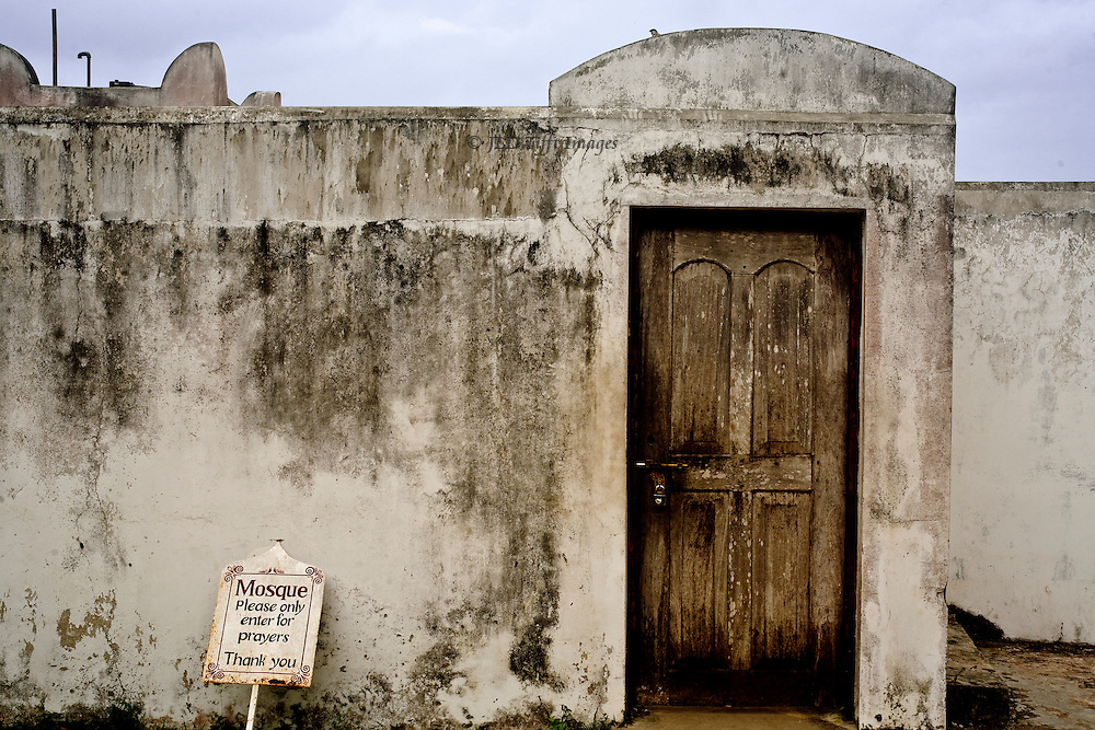 """Locked wooden door of a simple plastered wall.  A sign alongside politely requests: """"Mosque.  Please enter only for prayers.  Thank you.""""  It is in a seaside village in Zanzibar."""