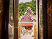 """22 JULY 2013 - PHRA PHUTTHABAT, THAILAND:  A woman prays in front of the Mondop (chapel) before the Tak Bat Dok Mai at Wat Phra Phutthabat in Saraburi province of Thailand, Monday, July 22. Wat Phra Phutthabat is famous for the way it marks the beginning of Vassa, the three-month annual retreat observed by Theravada monks and nuns. The temple is highly revered in Thailand because it houses a footstep of the Buddha. On the first day of Vassa (or Buddhist Lent) people come to the temple to """"make merit"""" and present the monks there with dancing lady ginger flowers, which only bloom in the weeks leading up Vassa. They also present monks with candles and wash their feet. During Vassa, monks and nuns remain inside monasteries and temple grounds, devoting their time to intensive meditation and study. Laypeople support the monastic sangha by bringing food, candles and other offerings to temples. Laypeople also often observe Vassa by giving up something, such as smoking or eating meat. For this reason, westerners sometimes call Vassa the """"Buddhist Lent.""""    PHOTO BY JACK KURTZ"""