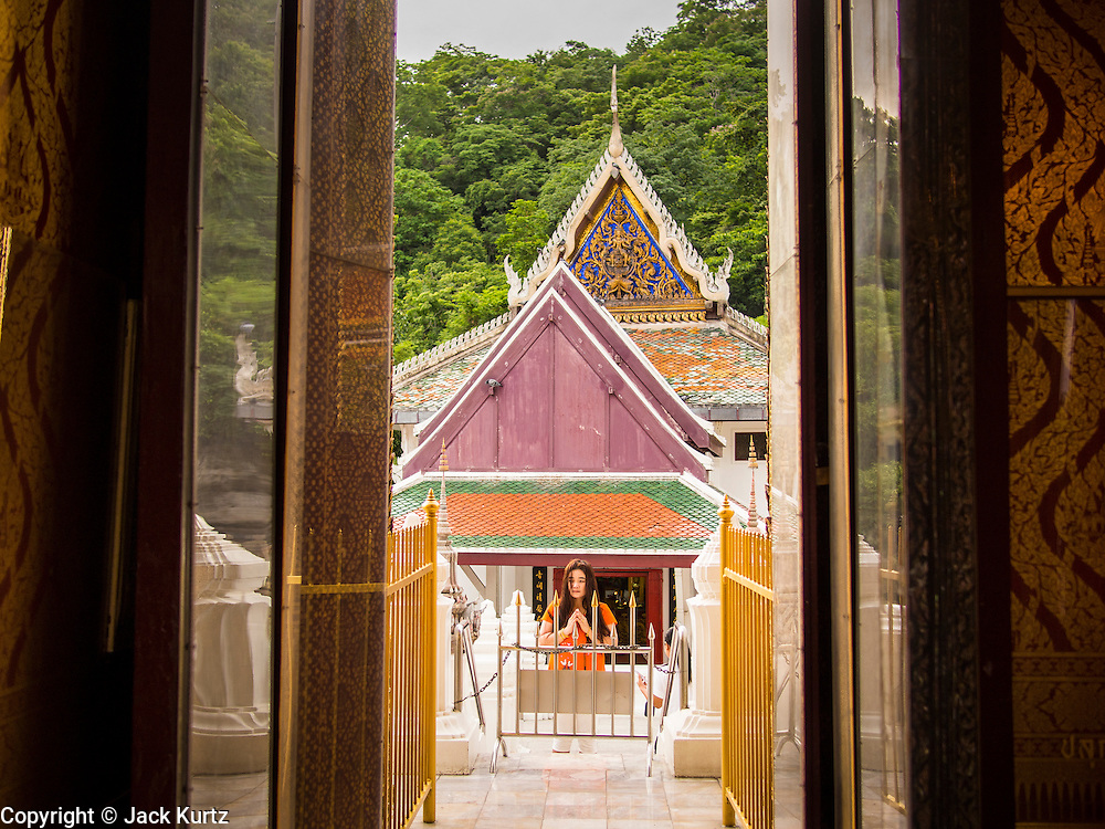"22 JULY 2013 - PHRA PHUTTHABAT, THAILAND:  A woman prays in front of the Mondop (chapel) before the Tak Bat Dok Mai at Wat Phra Phutthabat in Saraburi province of Thailand, Monday, July 22. Wat Phra Phutthabat is famous for the way it marks the beginning of Vassa, the three-month annual retreat observed by Theravada monks and nuns. The temple is highly revered in Thailand because it houses a footstep of the Buddha. On the first day of Vassa (or Buddhist Lent) people come to the temple to ""make merit"" and present the monks there with dancing lady ginger flowers, which only bloom in the weeks leading up Vassa. They also present monks with candles and wash their feet. During Vassa, monks and nuns remain inside monasteries and temple grounds, devoting their time to intensive meditation and study. Laypeople support the monastic sangha by bringing food, candles and other offerings to temples. Laypeople also often observe Vassa by giving up something, such as smoking or eating meat. For this reason, westerners sometimes call Vassa the ""Buddhist Lent.""    PHOTO BY JACK KURTZ"