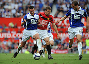 Michael Owen of Manchester United takes on Franck Queudrue and Roger Johnson of Birmingham City during the Barclays Premier League match between Manchester United and Birmingham City at Old Trafford on August 16, 2009 in Manchester, England.