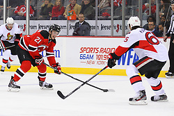 Dec 18, 2013; Newark, NJ, USA;  New Jersey Devils center Andrei Loktionov (21) skates with the puck while being defended by Ottawa Senators defenseman Erik Karlsson (65) during the second period at the Prudential Center.