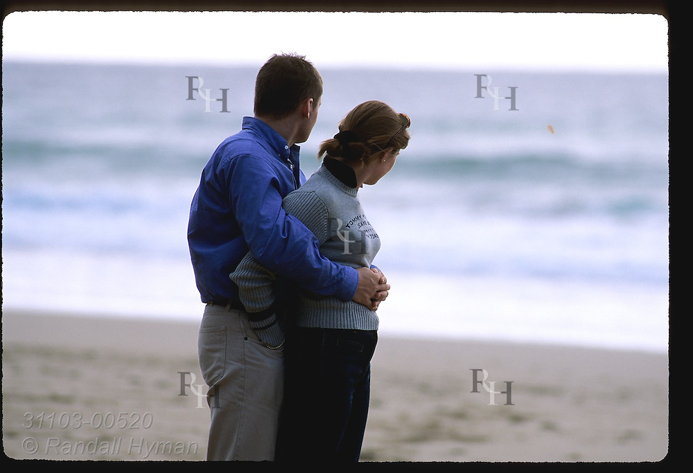 Young lovers embrace while viewing the waters off Coumeenole Beach near Dunmore Head on the Dingle Peninsula; Ireland.