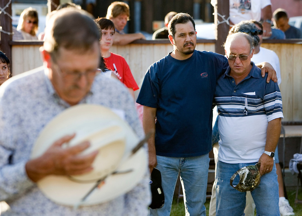 Steve Tenner, of Helper, left front a miner of 3o years, Cesar  Sanchez, center, brother of the trapped miner Manual Sanchez and Jim Hanna, underground forman of the Crandall Canyon Mine bow their heads during a prayer as they attended a auction, raffle and prayer meeting to raise money for the families of the miner's killed and injured in the Crandall Canyon Mine collapse and rescue. The event was held in downtown Helper, Utah Friday, August 24, 2007.  August Miller/ Deseret Morning News