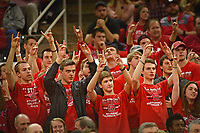 Student Wolfpack Club members raise their Wuf Hands in support of a basketball player shooting free throws.