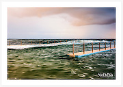 The tones in this image were captured during a few moments of magical light, very late on a spring afternoon. A brilliant rainbow, outside of this frame, reflected a subtle, sweet light over the pool. An exposure time of 0.5 seconds gave a painted effect to the water [South Curl Curl ocean pool, NSW]<br />