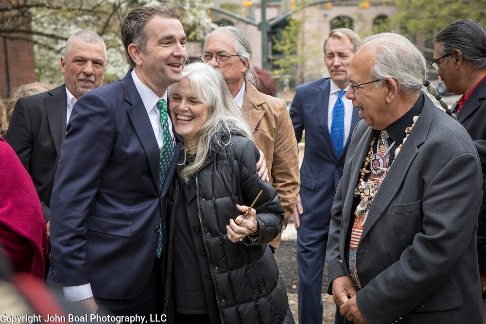 Virginia Governor, Ralph Northam, and Frances Broaddus-Crutchfield, embrace after the ceremonial ribbon cutting at the dedication ceremony for Mantle: Virginia Indian Tribute, a monument designed on Virginia State Capitol Square, in Richmond, Virginia, on Tuesday, April 17, 2018. Broaddus-Crutchfield is a member of the Virginia Indian Commemorative Commission and major donor to the monument. Broaddus-Crutchfield also read a poem she wrote during the ceremony. John Boal Photography