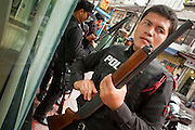 """May 12 - BANGKOK, THAILAND: Thai security personnel load and check their weapons before going on duty near the front line of the Red Shirt protesters and security forces in Sala Daeng intersection Wednesday. The Thai government said Wednesday that time has run out for """"Red Shirt"""" protesters in Ratchaprasong and Sala Daeng intersections in Bangkok and that a crackdown could come at any time. As news of the anticipated crackdown spread, Red Shirt protesters continued with an almost festive mood at their main stage but many of the sleeping areas around the protest site appeared to be empty. No official estimates on crowd size are available.  Photo by Jack Kurtz"""