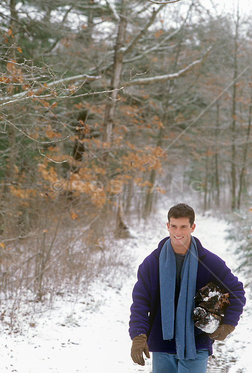 man walking on a snow covered path in the woods with firewood under his arm
