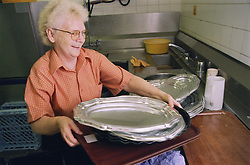 Senior catering assistant standing at plate wash in hospital kitchen,