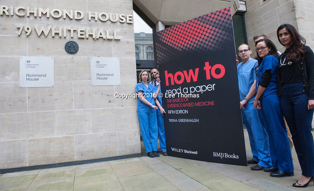 """Whitehall, London, UK. 21st January, 2016. Doctors wearing scrubs carry - from opposite Downing Street to Richmond House, The department of Health - a giant mock up of the 5th edition of """"How to Read a Paper – The Basics of Evidence-Based Medicine"""" by Trisha Greenhalgh.  // Lee Thomas, Flat 47a Park East Building, Bow Quarter, London, E3 2UT. Tel. 07784142973. Email: leepthomas@gmail.com. www.leept.co.uk (0000635435)"""