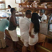 A well stocked bakery in the Habana Vieja section that has a large influx of tourists. Cubans manage their daily life whether  waiting for overcrowded busses or doubling up on old classic cars and motorcycles or walking everywhere. Locals and tourist walk and window shop in La Habana Vieja. <br />