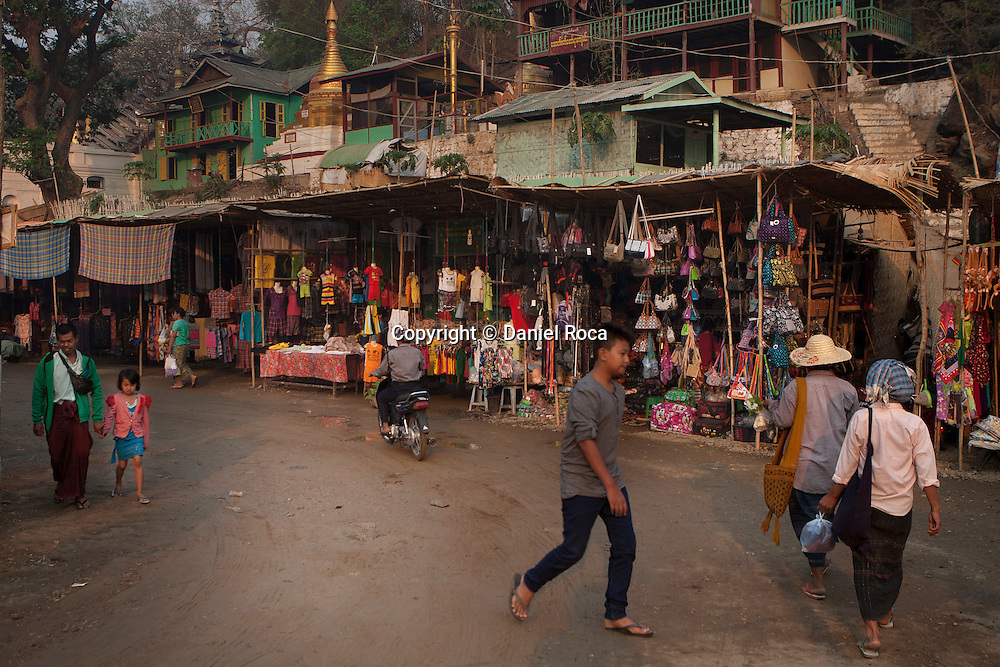 The streets of Shwet Set Taw are full with shops of all kinds, from textiles and accessories to offerings for the temples. Shwet Set Taw, Magwai Division, Myanmar. February 2014.