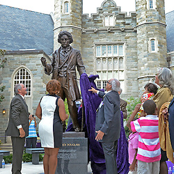 Photos by Tom Kelly IV<br /> Clifford DeBaptiste (right) with his family behind him, West Chester University President Greg Weisenstein (left) and Mildred Joyner (center) unveil the statue during the dedication of the Frederick Douglass statue at West Chester University, Tuesday afternoon October 1, 2013.