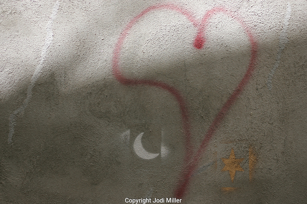 A spray painted red heart, white moon and yellow star on a stucco wall.