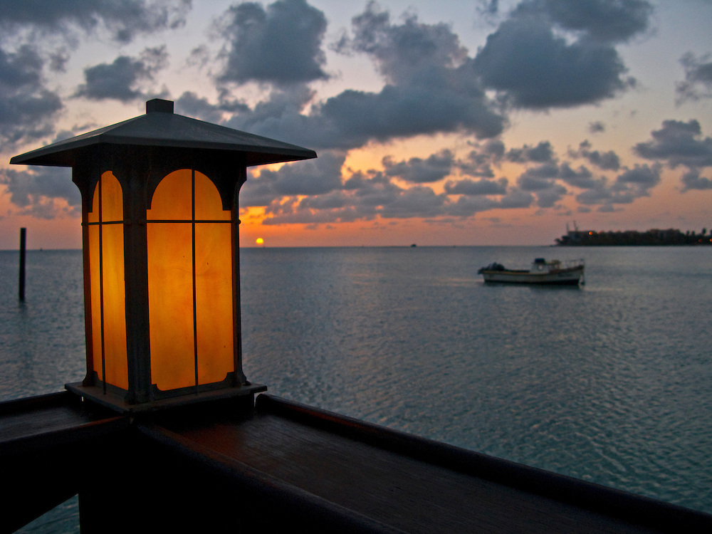 A lantern lights up as the sun sets in Aruba.