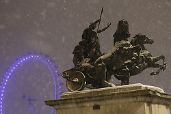 © licensed to London News Pictures. London, UK 04/02/2012. The Statue of Boudicca outside Parliament, with the London Eye seen in the background as London is hit by snow tonight (04/02/12). Photo credit: James Gourley/LNP