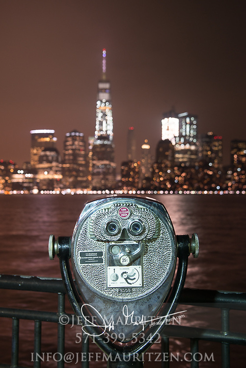 Coin-operated binoculars point towards downtown Manhattan and the One World Trade Center in NYC.