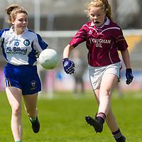Niamh O'Loughlin gets the ball forward ahead of Grace McCusker.<br /> <br /> Lisdoonvarna Parish Schools v Scoil Réalt na Mara, Kilkee/Moyasta NS, in Division 3  Clare Primary Schools Ladies Football Finals at Cusack Park, Ennis, Co. Clare