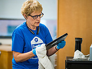 """19 MARCH 2020 - DES MOINES, IOWA: CONNIE BROICH, a worker for Des Moines Public Schools, cleans and disinfects laptops at Central Campus, a high school in the Des Moines Public Schools system. The district has more than 35,000 laptops and tablet computers that need to be disinfected before students come back. Des Moines schools are closed for at least 30 days because of the coronavirus and officials are using the time to """"deep clean"""" and sanitize each school. On Thursday morning, 19 March, Iowa reported 38 confirmed cases of the Coronavirus. Restaurants, bars, movie theaters, places that draw crowds are closed for at least 30 days. There are no """"shelter in place"""" orders in effect anywhere in Iowa but people are being encouraged to practice """"social distancing"""" and many businesses are requiring or encouraging employees to telecommute.      PHOTO BY JACK KURTZ"""