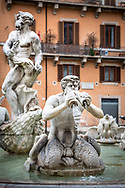 Fontana del Moro Fourntain / Moor Fountain in Piazza Navona, Rome. The moor sculpture by Bernini stands left as a triton blows water through shells in front of an orange wall with windows and shutters.