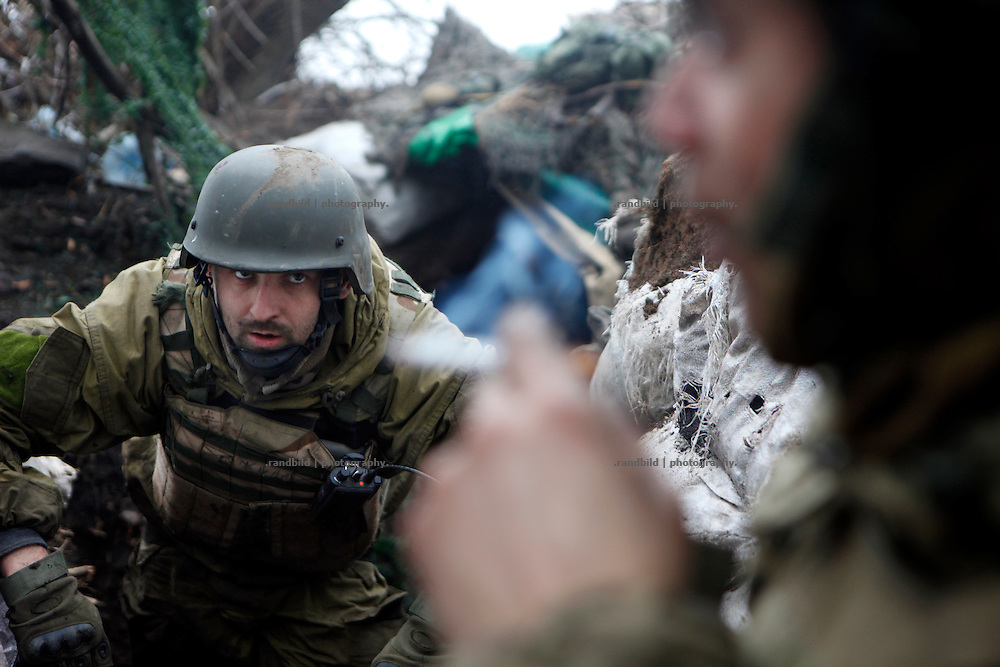 An ukrainian comrade of the Prawy Sector unit watches Charlie smoking in the trench and ducks down as grenates are being launched from the seperatist side towards. them.<br />