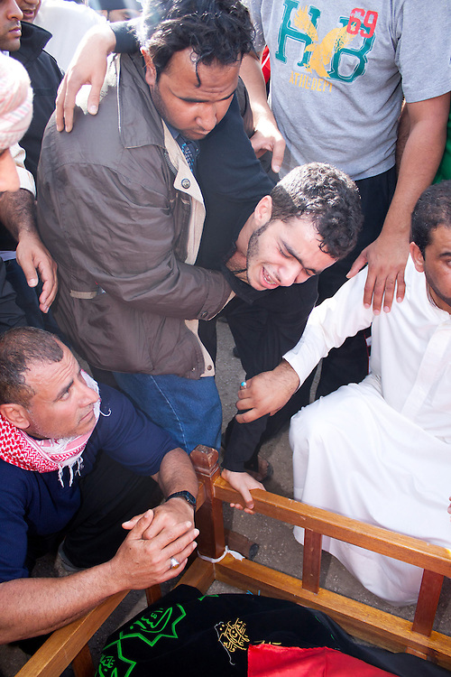 The brother of Ali Al Almoumen, the third person to be buried in Sitra on Friday, 18/02/11, weeps over his grave has he is buried. Al Almourmen was killed on Wednesday at the Pearl Roundabout.