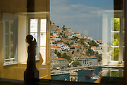 Window looking out onto town with reflections from the inside, Hydra, Greece.