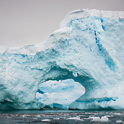 A large hole has been carved out of an iceberg in Curtis Bay, Antarctica, creating an arch.