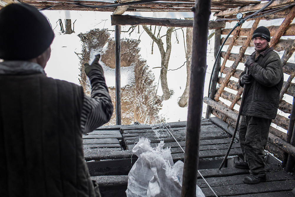 SNEZHNE, UKRAINE - JANUARY 25, 2015: Sergei Danshin, left, and Dmitry Kontratenko operate winches to haul up loads of coal at the small private coal mine where they work in Snezhne, Ukraine. The mine produces approximately 15 tons of coal per day with a crew of four men. CREDIT: Brendan Hoffman for The New York Times