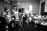 One of the cramped rooms at the Town and Country Motel is the combined dining room, play room and bedroom for the six kids of Cora McNeil and Mike Jackson. At least four of kids sleep together on the mattress on the floor each night. Josh Brenton, 16, at left, hold Christian, 1, while Morgan, on chair, Shannon, Ryan, Jordan, and Dylan play in the room before going to bed. Brenton lives in a motel down the road but comes to the Town and Country to play because he is the only kid living at his motel.  (Mike Fender Photo) w/ story
