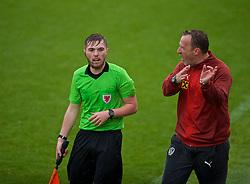 NEWPORT, WALES - Monday, October 14, 2019: Assistant referee Connor Thomas (L) and Austria's head coach Rupert Marko during an Under-19's International Friendly match between Wales and Austria at Dragon Park. (Pic by David Rawcliffe/Propaganda)