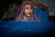 Kabul: 70 year old Bibi Zamogan at her makeshift home at Tamil Mill Bus site in Kabul city. She shares the one room makeshift home with her 20 year old daughter Hanifer...Tajik and Pashtun families live side by side without any major conflict at the Tamil Mill Bus site. Over 70% of the families are returnees from the period 2002-2004 who are unable to achieve sustainable reintegration in their places of origin and subsequently drifted to Kabul City in search of work...There is a nearby school which is accessible to the children but the poor economic circumstances of the many families oblige them to send their children out to work. low levels of literacy, particularly amongst the women, limit their access to employment other than the lowest paid daily wage labor...Afghanistan. /UNHCR/Jason Tanner/February 2011