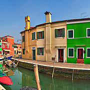 Bright coloured houses on coast of channel in Burano island Venice Italy