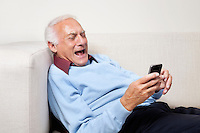 Happy elderly man using cell phone at home