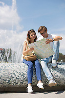 Couple reading map while sitting on fountain