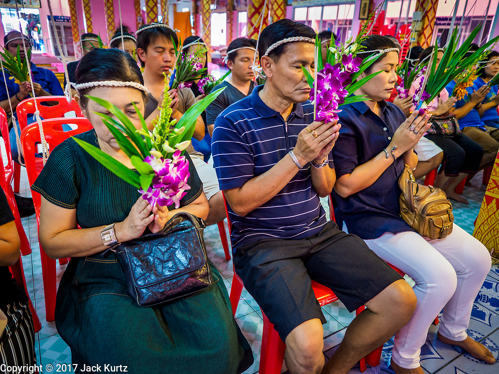 "24 JUNE 2017 - BANG KRUAI, NONTHABURI: People pray during a ""resurrection"" or rebirthing ceremony at Wat Ta Kien (also spelled Wat Tahkian), a Buddhist temple in the suburbs of Bangkok. The strings around their heads are connected to a web of strings that is supposed to amplify the power of the prayers. People go to the temple to participate in a ""Resurrection Ceremony."" Thai Buddhists believe that connecting people by strings around their heads, which are connected to a web of strings suspended from the ceiling, amplifies the power of the prayer. Groups of people meet and pray with the temple's Buddhist monks. Then they lie in coffins, the monks pull a pink sheet over them, symbolizing their ritualistic death. The sheet is then pulled back, and people sit up in the coffin, symbolizing their ritualist rebirth. The ceremony is supposed to expunge bad karma and bad luck from a person's life and also get people used to the idea of the inevitability of death. Most times, one person lays in one coffin, but there is family sized coffin that can accommodate up to six people. The temple has been doing the resurrection ceremonies for about nine years.     PHOTO BY JACK KURTZ"