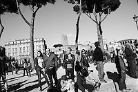 ROME, ITALY - 21 APRIL 2013: Pedestrians relaxing a suny Sunday afternoon watch  supporters of the Five-Star Movement on their way to the Colosseum for a rally the day after the re-election of President Giorgio Napolitano,  in Rome, Italy, on April 21, 2013.<br /> <br /> Italy's lawmakers re-elected 87-year-old President Giorgio Napolitano on Saturday in a bid to break the country's political gridlock, as protestors outside parliament protested agains the result. Giorgio Napolitano won with a  majority of 738 ballots out of 1,007 possible votes, ahead of leftist academic Stefano Rodota, backed by the the anti-establishment Five Star Movement, who scored 217.