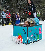 "Avi Bartlett and Olivia Salesky ride inside the ""Coral Reef"" while teammate Brianna Salanitro runs along side during Gilford Parks and Recreation annual Cardboard Derby race at the Outing Cluyb Wednesday morning.  (Karen Bobotas/for the Laconia Daily Sun)"