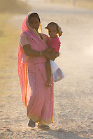 Woman holding her baby and walking on a dusty road in Nepalganj, Nepal