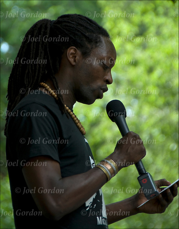 African American speaker on outdoor stage with microphone at Dancefest in Tompkins Square Park introducing the next dance performers.