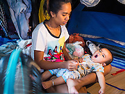 18 JANUARY 2015 - BANGKOK, THAILAND:  A woman who is a Chinese opera performer feeds her child in their tent beneath the stage at the Sai Yong Hong Opera Troupe performance at the Chaomae Thapthim Shrine, a Chinese shrine in a working class neighborhood of Bangkok near the Chulalongkorn University campus. The troupe's nine night performance at the shrine is an annual tradition and is the start of the Lunar New Year celebrations in the neighborhood. The performance is the shrine's way of thanking the Gods for making the year that is ending a successful one. Lunar New Year, also called Chinese New Year, is officially February 19 this year. Teochew opera is a form of Chinese opera that is popular in Thailand and Malaysia.             PHOTO BY JACK KURTZ
