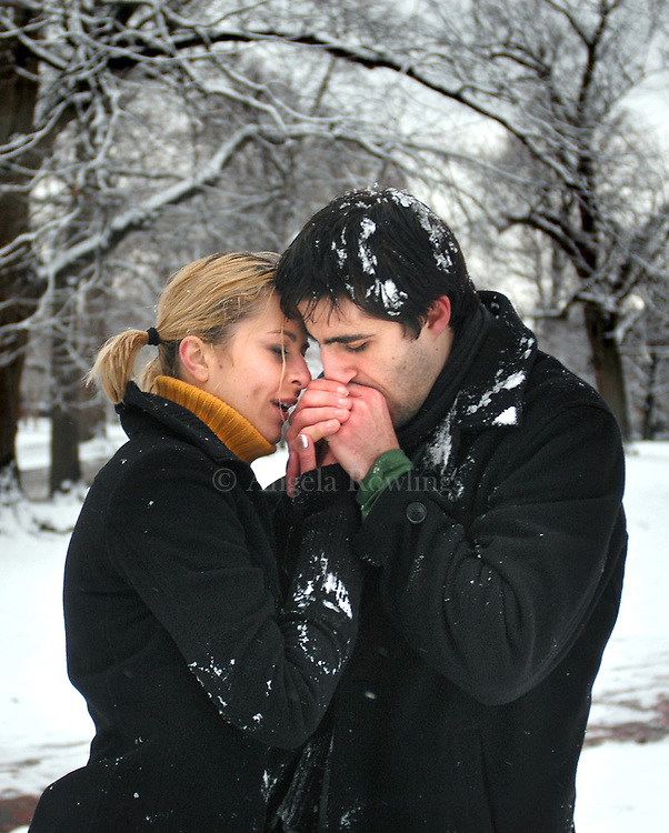 Francesco Epifania kisses Tatiana Filipovich's hands to warm them after a snow ball fight on the Boston Common.