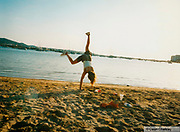 Girl doing a hand stand on the beach, Ibiza, 1998