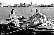 "Riverscape, with the city in the distance.  In the foreground, a wooden rowboat, its oars held by the husband, while his wife sits opposite smiling gently.  Though clearly poor they radiate dignity, kindness, and trust.  A water jar hangs off one gunwale, and a fishing net off the opposite gunwale.  A canvas covers the rest of their belongings in the prow.  See the book ""Khuul Khaal"" by Nayra Atiya to learn more about them.  The rowboat is their home."