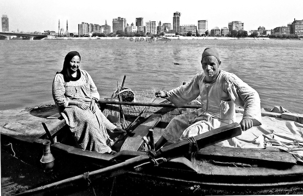 """Riverscape, with the city in the distance.  In the foreground, a wooden rowboat, its oars held by the husband, while his wife sits opposite smiling gently.  Though clearly poor they radiate dignity, kindness, and trust.  A water jar hangs off one gunwale, and a fishing net off the opposite gunwale.  A canvas covers the rest of their belongings in the prow.  See the book """"Khuul Khaal"""" by Nayra Atiya to learn more about them.  The rowboat is their home."""