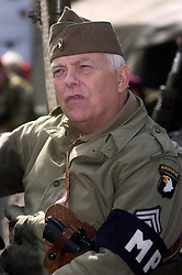 "A reenactor portrays a sergeant from the American 101st Airborne ""Screaming Eagles"" armed with a Colt 45 Automatic Pistol carried in a shoulder holster and wearing an MP (Military Police) Armband  <br />