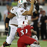 Louisville Cardinals linebacker Champ Lee (31) tackles Miami Hurricanes quarterback Stephen Morris (17)during the NCAA Football Russell Athletic Bowl football game between the Louisville Cardinals and the Miami Hurricanes, at the Florida Citrus Bowl on Saturday, December 28, 2013 in Orlando, Florida. (AP Photo/Alex Menendez)