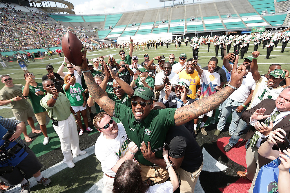 Tim Alexander raises his arms in triumph after walking the game-ball from the 40-yard line to midfield before UAB's first football game since the team was disbanded in 2014. Alexander was in a car wreck in 2006 that left him paralyzed from the waist down. He now serves as the Director of Character Development for the UAB Football team. <br /> Alabama A&amp;M Bulldogs vs. UAB Blazers at Legion Field in Birmingham, Ala. on Saturday, Sept. 2, 2017.<br /> Zach Bland/For UAB Athletics